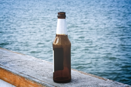 Empty Bottle of Beer On the Bridge By the Sea