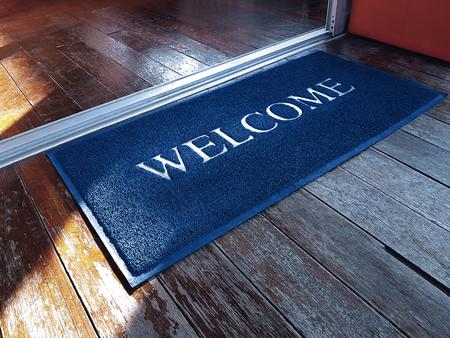 Blaue Fußmatte mit Begrüßungstext vor dem Laden Standard-Bild