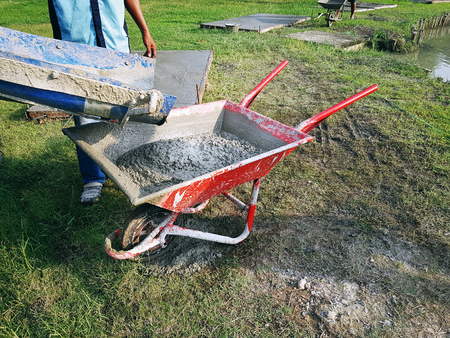 Worker Pouring Mixed Cement into Red Wheelbarrow at Construction Site