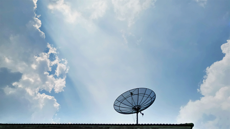 Low Angle View of Satellite Receiver Dish on the Roof Against Blue Cloudy Sky 版權商用圖片