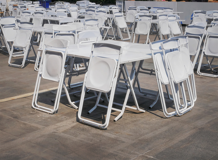 Groups of White Collapsible Chairs and Tables for the Event