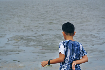 Boy Standing on the Beach Looking at the Sea