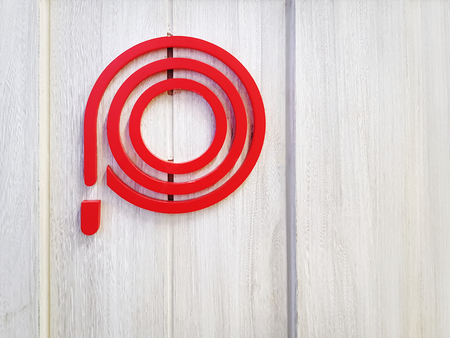 Red Symbol of Fire Hose Reel on Wooden Wall