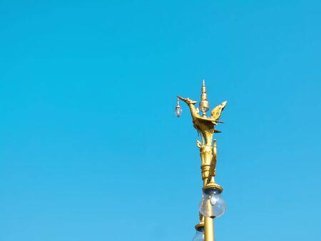 Traditional Thai Golden Bird Lamp Post Against Blue Sky