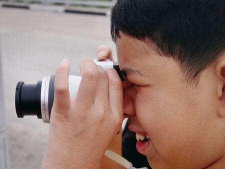 Close-up Shot of Kid Taking Photos with Mirrorless Camera