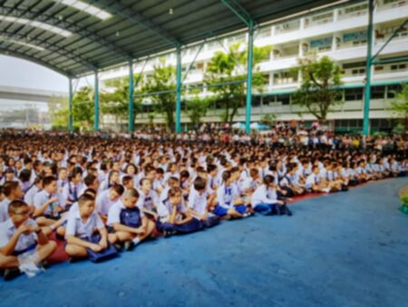 Blurred Background of Group of Thai Students in Uniform Sitting on Floor