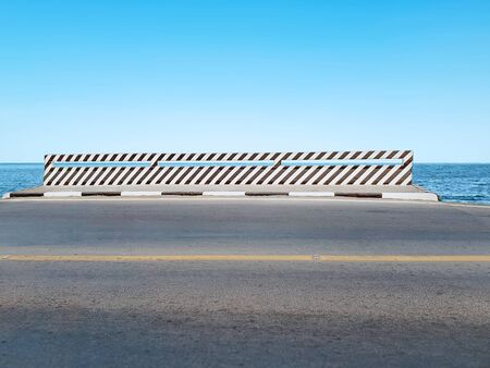 Bridge with Black and White Striped Paint Against Blue Sea and Sky