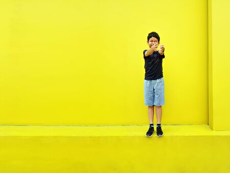Smiling Child in Casual Clothes Standing Against Yellow Wall