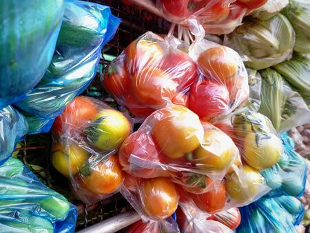 Bunch of Fresh Ripe Tomatoes in Bags at Market Stall