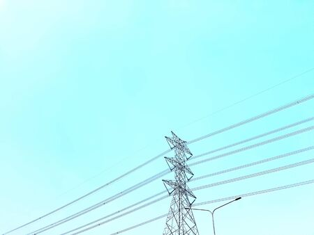 Low Angle View of High Voltage Towers and Power Lines Against Clear Blue Sky