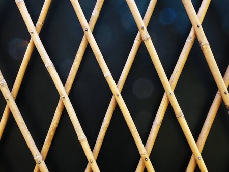 Full Frame Decorative Bamboo Fence Pattern Against Black Wall 스톡 콘텐츠