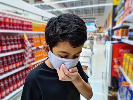 Kid Standing at the Aisle Wearing Medical Mask with Head Down