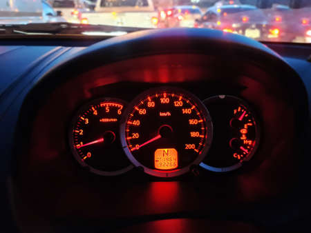 Yellow Red Illuminated Speedometer Console Against Blurred Traffic Background