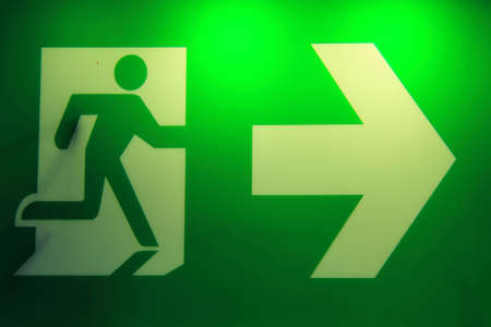 Emergency exit sign in a building glowing green  photo