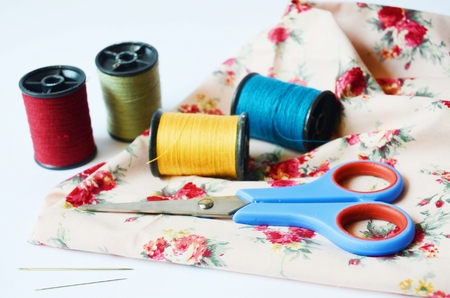 sewing kit: sewing tools and colored tape Sewing kit   Scissors, bobbins with thread and needles on white background