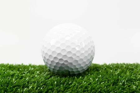 The golf ball is placed on a green lawn.