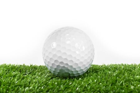White golf ball placed on a green lawn.