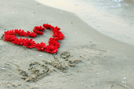 heart and flowers on beach background photo