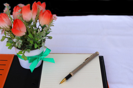 notebook , pen and flower on table