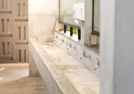 Stanless steel taps above concrete sink in shared toilet with yellow sunlight for background.