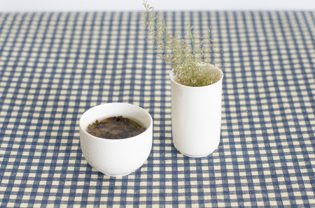 White tea cup on the table with a flower vase  photo