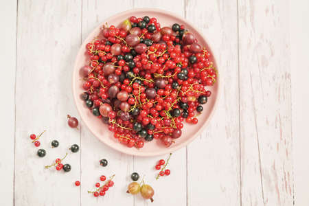 Colorful fresh berries on white background. Top view. Summer Organic Berry Cherry, Currant, Gooseberry. Agriculture, Gardening, Harvest Concept. Vitamins, Diet. Copy space. Healthly food, detox.