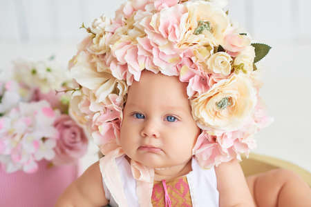 Sweet funny baby in hat with flowers. Easter greeting card, copyspace for your text. Poster for Easter holiday. Congratulations on Mother's Day. Cute baby girl 6 months wearing flower hat Imagens