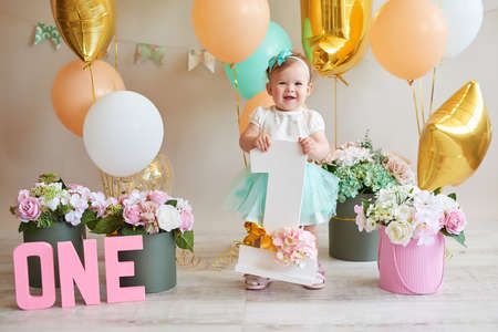 Little cheerful birthday girl with first cake. Happy infant baby celebrating his first birthday. Archivio Fotografico