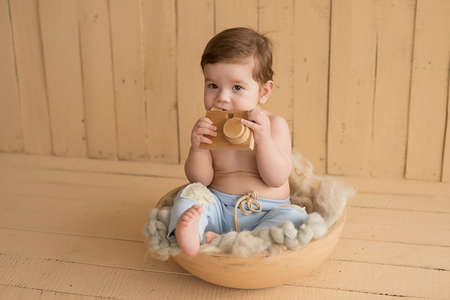 Baby boy sitting on crib. Children Protection Day. Happy childhood. Early child development. Educational wooden toys. Mother's day card. Child plays with toys. Happy baby 写真素材