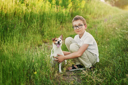 Children's Day. Happy little child boy having fun with dog pet Jack Russell Terrier on field. Summer walk. Childhood concept.Children camping with pet dog. Child lovingly embraces his pet dog