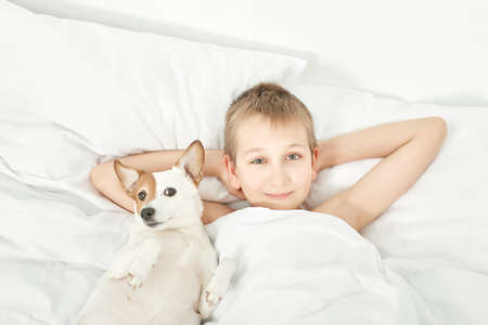 Two friends boy and dog lying together on bed. Boy on bed with dog jack russell terrier. Friendship concept. Cute little boy with funny dog on bed at home. Young Boy Hugging his Dog. Stock fotó
