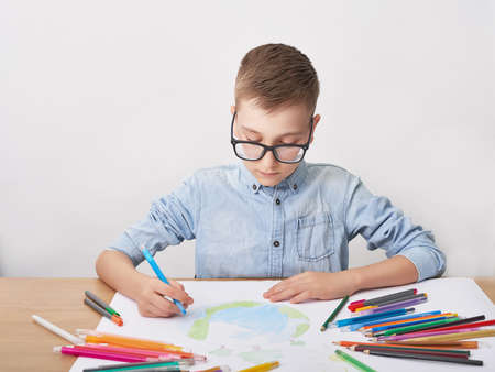 Child boy draws planet for earth day. Protection of enviroment, Mother Earth Day greeting and celebration. Save our planet! Concept of art learning and education, love earth, save world and unity. Stock fotó