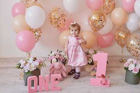 Smash cake party. Little cheerful birthday girl with first cake. Happy infant baby celebrating his first birthday. Decoration and photo zone for first year. One year baby celebration. Pink decor Banque d'images