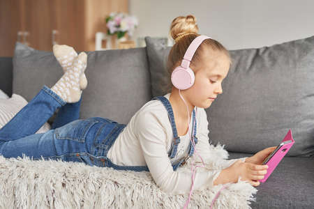 Girl laying on couch in headphones, listening to music with her smarthphone Little girl watching cartoons on her phone. Listening to an audiobook Foto de archivo