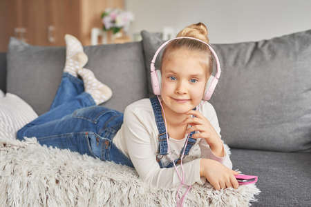 Girl laying on couch in headphones, listening to music with her smarthphone Little girl watching cartoons on her phone. Listening to an audiobook