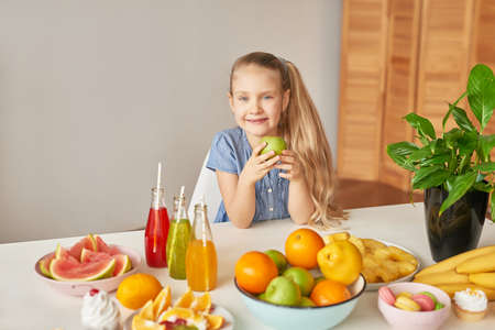 The girl eats fruit pineapple, watermelon, apples and drinks drinks from chia. Healthy food in the children's menu. Happy child with fruits and fresh juice in kitchen, kids healthy eating concept