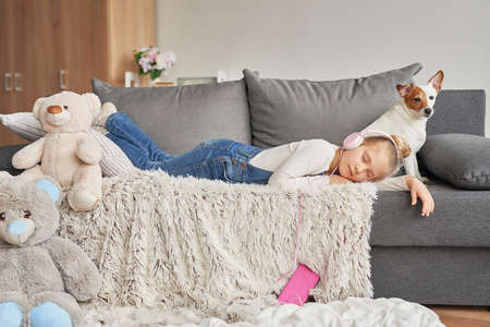 Girl and dog laying on couch in headphones, listening to music with her smarthphone. Little girl watching cartoons on her phone. Listening to an audiobook Foto de archivo