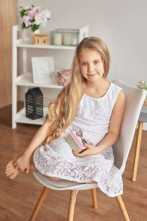 欣喜若狂的小女孩拿着礼物。可爱的生日会女孩生日礼物盒。漂亮的小女孩送礼物。母亲节礼物。妇女节贺卡。