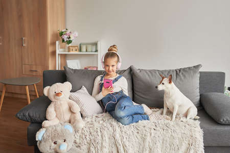 Girl and dog laying on couch in headphones, listening to music with her smarthphone. Little girl watching cartoons on her phone. Listening to an audiobook