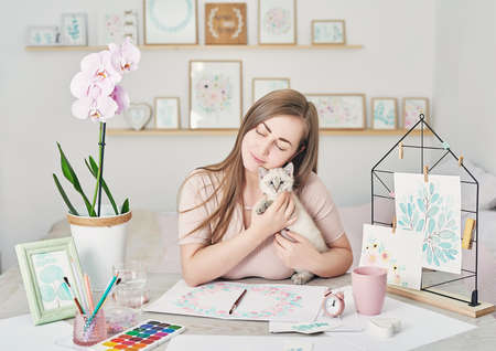Inspiration art creation. Creative painting hobby. Woman artist drawing beautiful floral watercolor design. Art studio. In artistic workshop. Woman and cute kitten. Friendship and love concept. Stok Fotoğraf