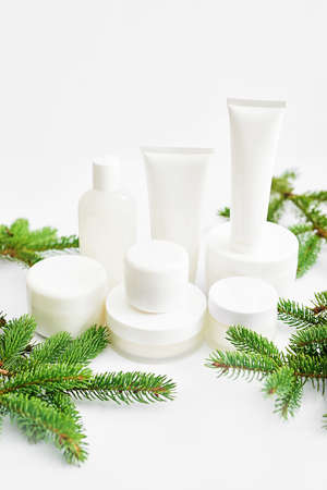 Christmas Beauty cosmetic products sale background. Flat lay composition with makeup products and fir branches on white background. Skin Care & Spa Products. Copy space