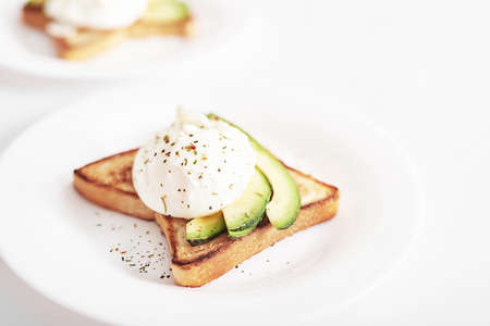 Toast with poached eggs and avocado. Healthy breakfast and food. Cozy morning. Nutrition for pregnant. Diet for women. Breakfast in hotel room or bed. Scrambled eggs sandwich Banque d'images