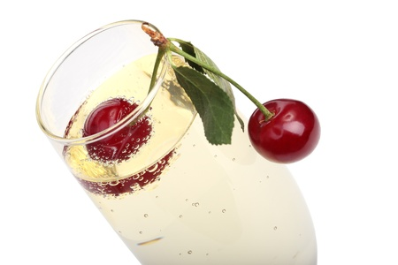 two ripe cherries into a glass with champagne, isolated on white photo