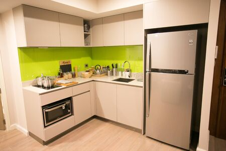 Small bright kitchen with oven and refrigerator