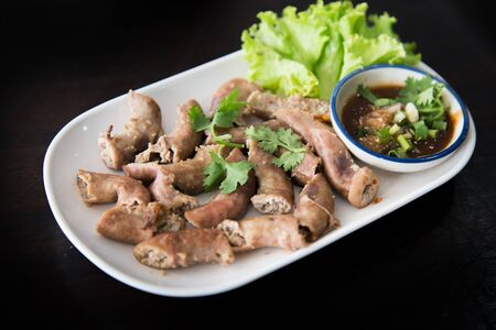 Thai-style deep-fried pork intestine with sweet black soy sauce, served in plastic plate by side of rice