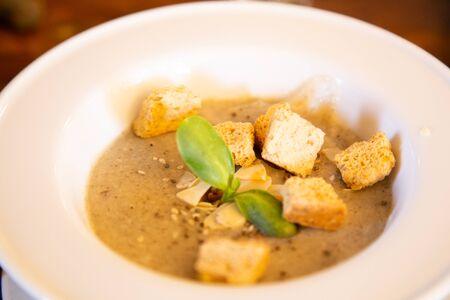 Zuppa di zucca con biscotti in un piatto bianco