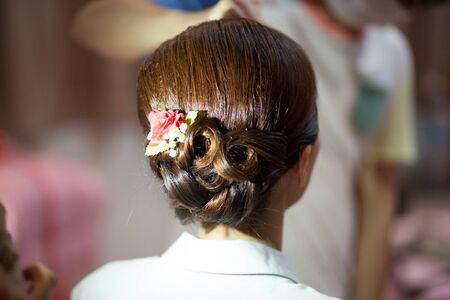 Hair stylist or florist makes the bride a wedding hairstyle Stock fotó