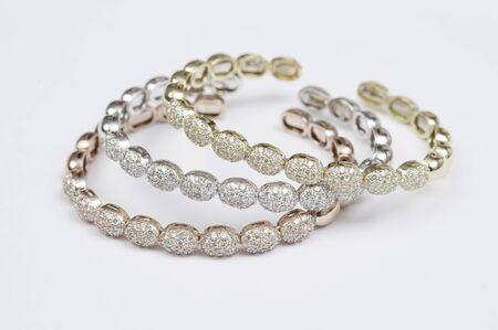 Conjunto de tres pulseras de oro y diamantes de colores.