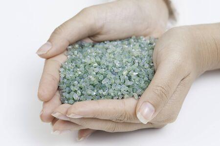 Rough green Peridot gemstone in hand on white background. Stock Photo