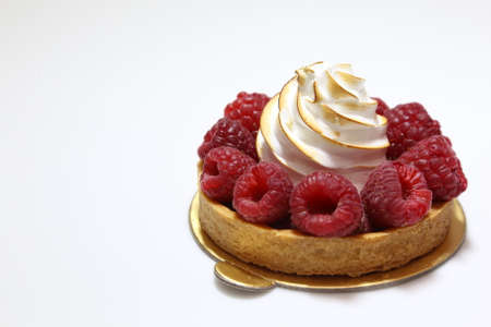 Meringue pie with raspberries on a white plate. Pie with bizet and fresh berries.
